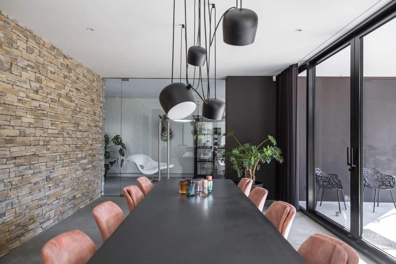 gevlinderde betonvloer in de eethoek, steens muur, roze velvet stoelen, zwarte tafel, hanglampen, glazen pui