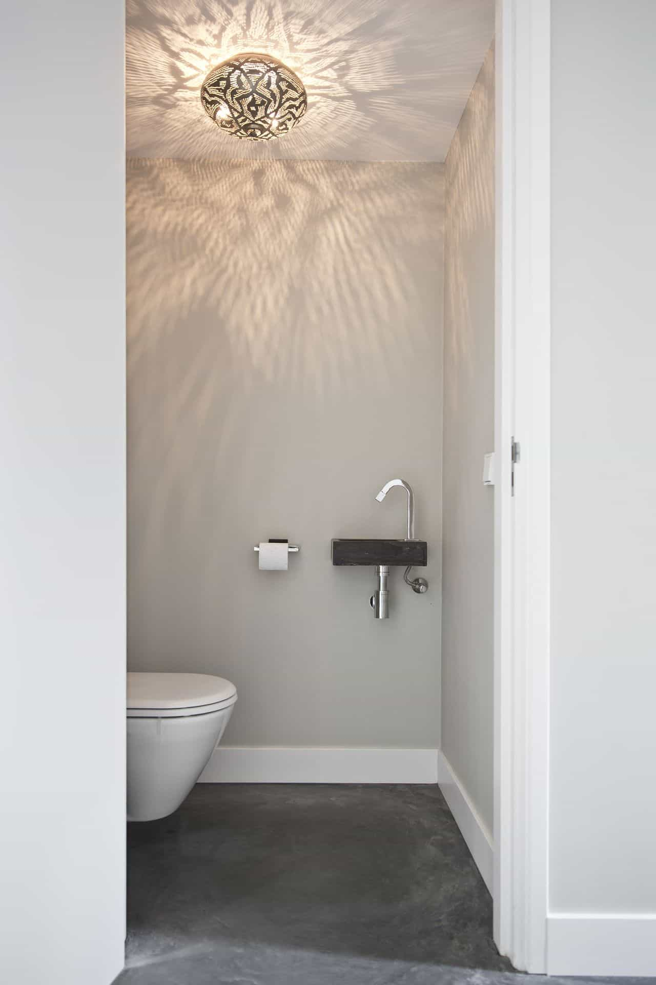 toilet met betonvloer, betonvloer in toilet, gevlinderd woonbeton in toiletgedeelte