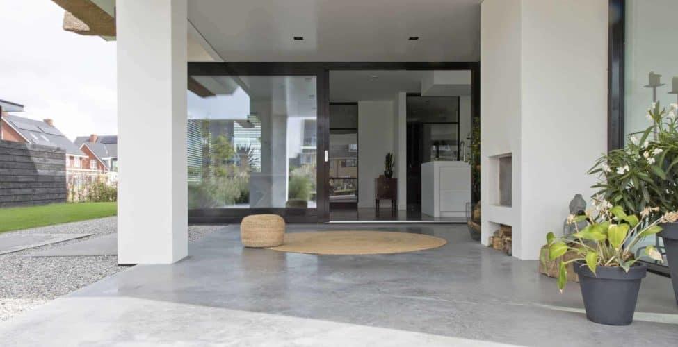 Doorlopende betonvloer naar buiten, gevlinderd beton terras, betonvloer onder afdak