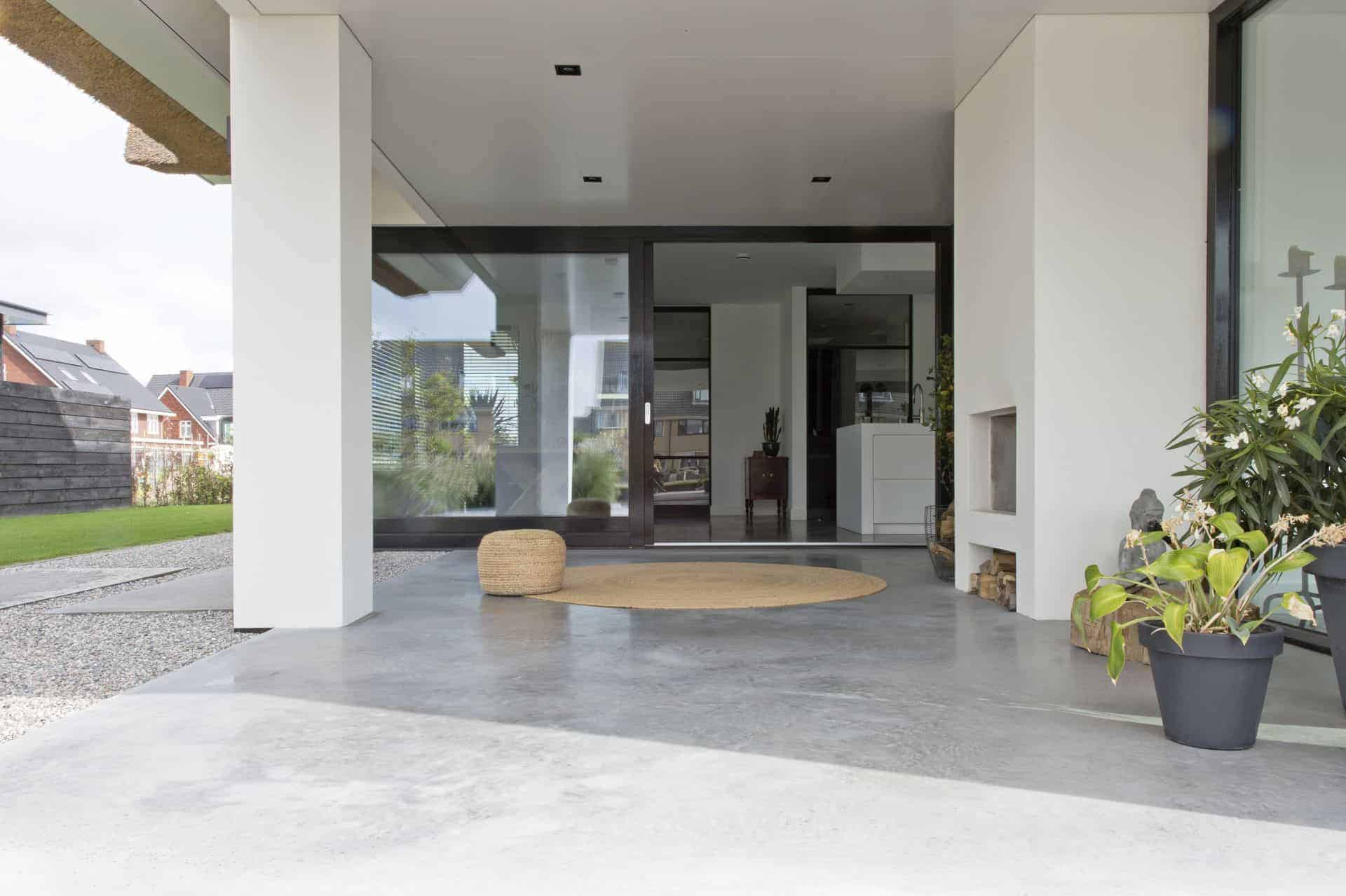betonvloer buiten, doorlopende betonvloer naar buiten, gevlinderd beton terras, betonvloer onder afdak