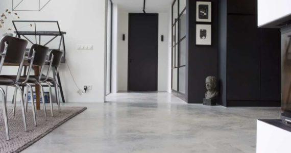 Gang met woonbeton, stalen deuren met woonbeton, grijs in het interieur, betonvloer interieur, interieur met betonvloer