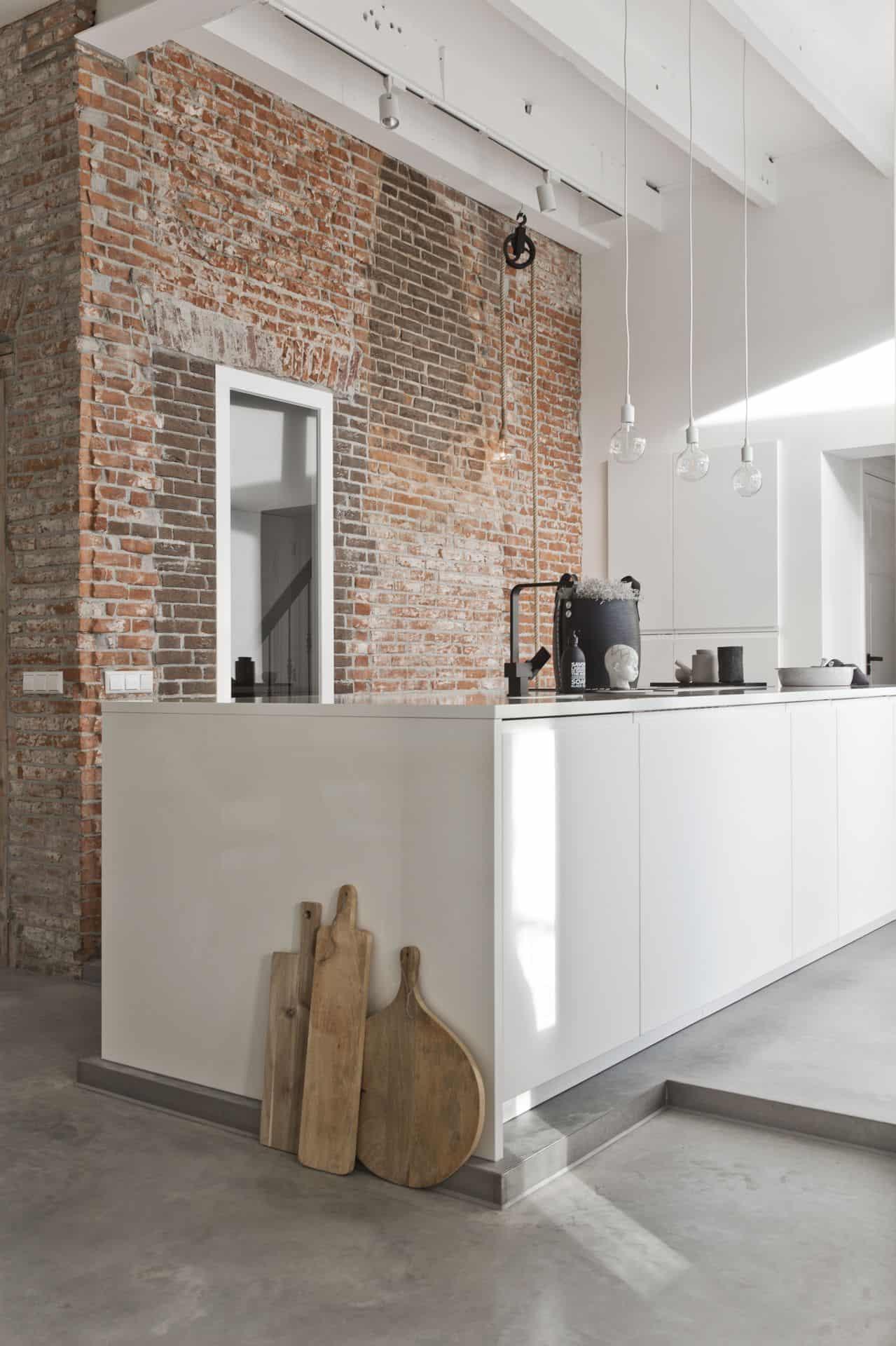 betonnen vloer met witte keuken en stenen muur