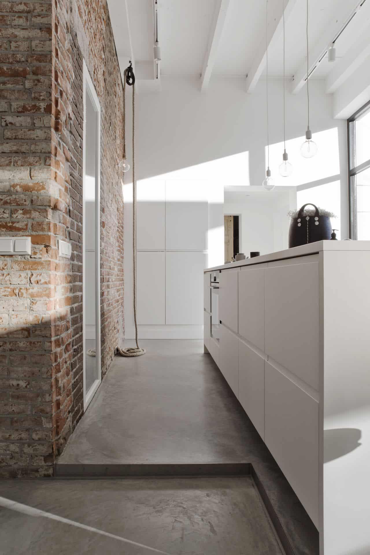 betonvloer met witte keuken en stenen muur, woonkeuken met betonvloer,